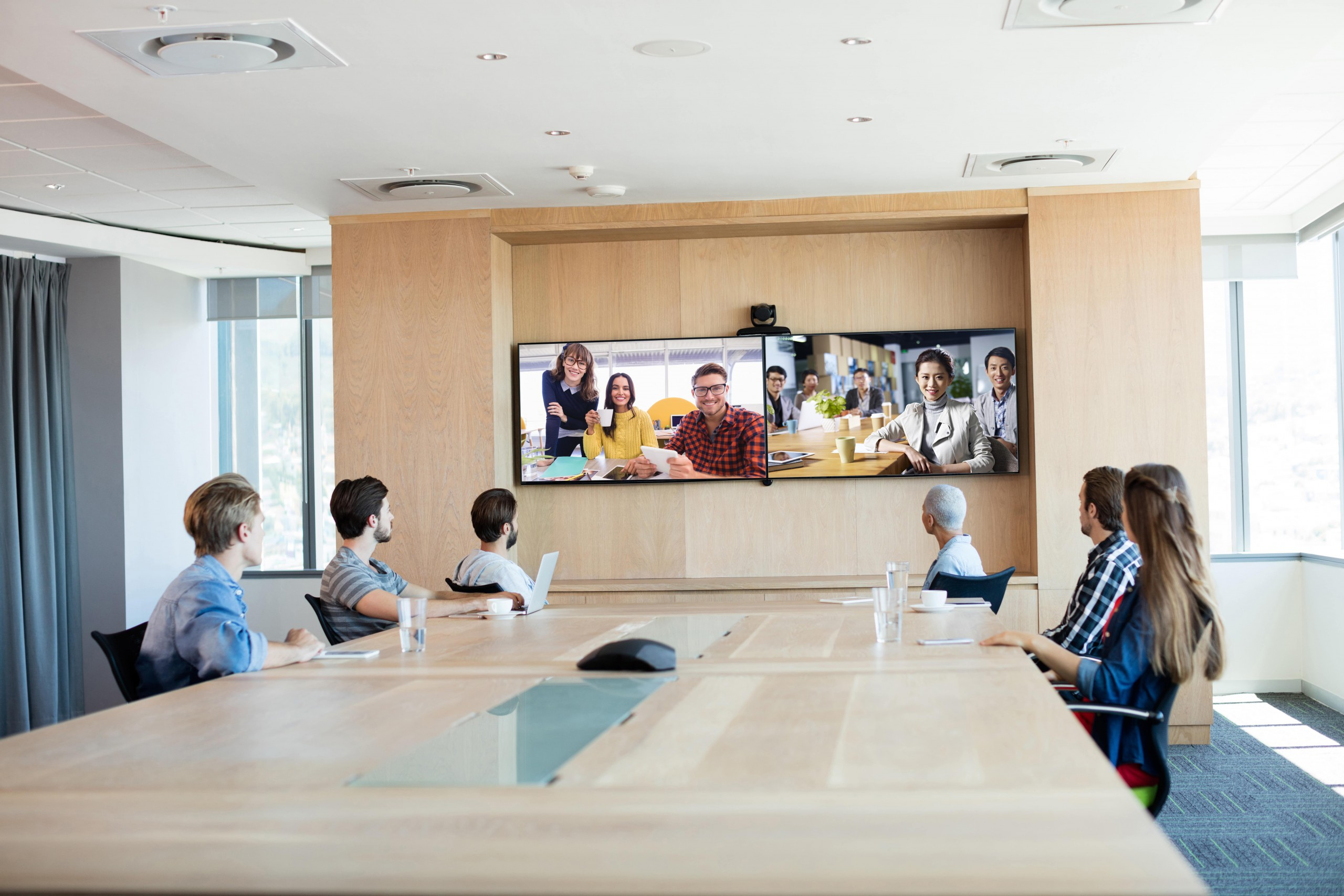 conference room with people video chatting with other offices